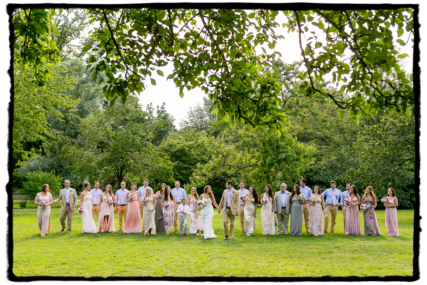 Rorie & Adam's wedding party in summer hues  take a stroll at The Brooklyn Botanic Garden.