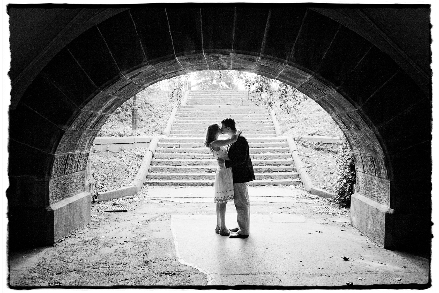 Engagement Portraits: a kiss is framed nicely in a tunnel at Central Park.