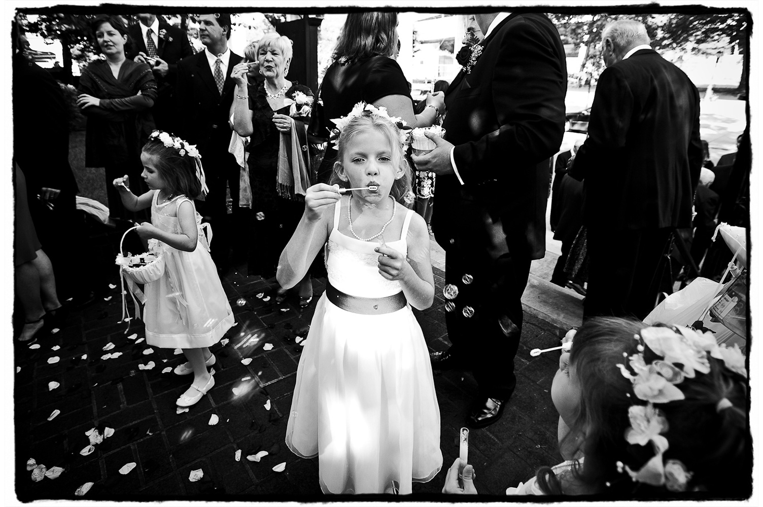 A flower girl blows bubbles at the base of church steps in Brooklyn.