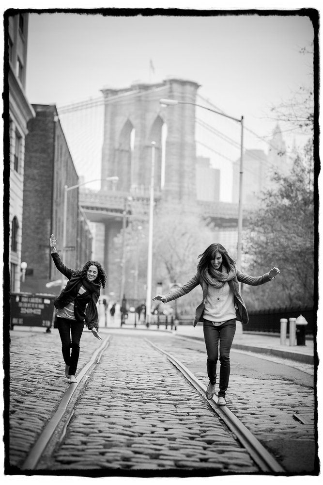 Engagement Portraits: Lara & Nicole on a cobblestone street with the Brooklyn Bridge behind them.