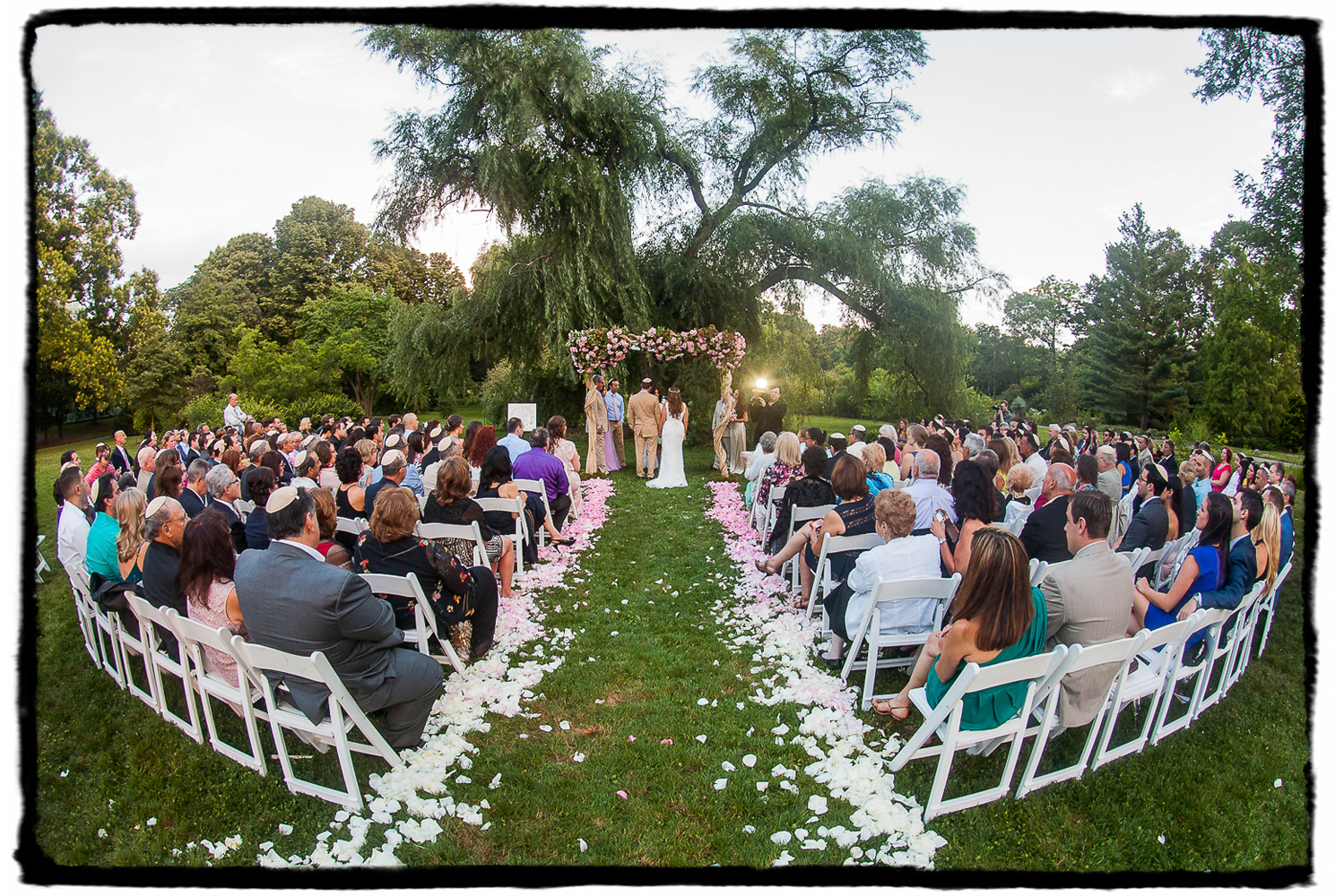 Rorie & Adam's summer ceremony under a willow tree with ombre rose petals in the aisle at Brooklyn Botanic Garden.