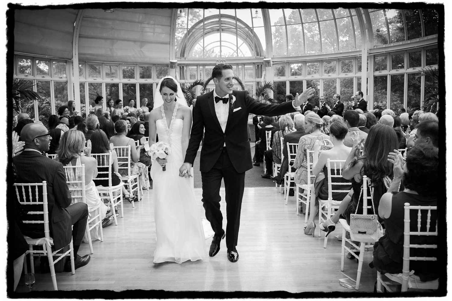 Jessica and Stephen wave to their guests as they walk back down the aisle in The Palm House at Brooklyn Botanic Garden.