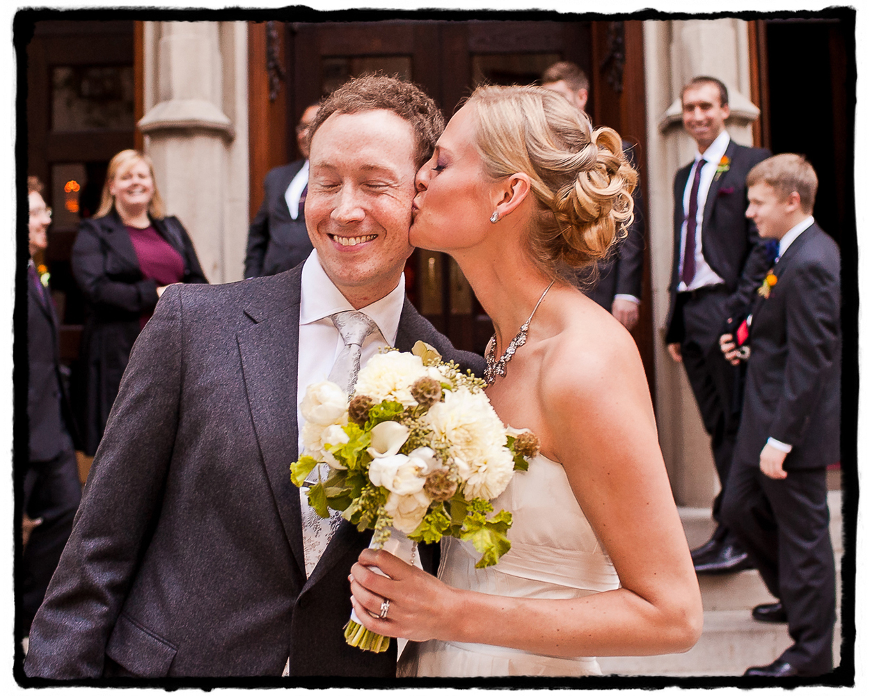 After their grand exit the bride bestows a spontaneous kiss on the groom's cheek on the steps of Blessed Sacrament on the upper west side.